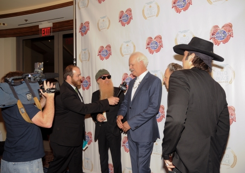 Andy Langer (L) interviews Billy Gibbons and Turk Pipkin while Jimmie Vaughan and Robert Rodriguez look on during the 10th Annual Nobelity Project Feed The Peace Awards at the Four Seasons Hotel on February 15, 2015 in Austin, Texas.
